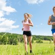 Sportive young couple jogging meadows sunny summer — Stock Photo #6138483