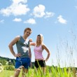 Sportive happy couple in meadows sunny day — Stock Photo