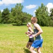 Sportive young couple jogging meadows sunny summer — Stock Photo