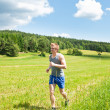 Sportive young man jogging meadows sunny summer — Stock Photo