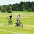 Sport happy couple riding bicycles in coutryside — Stock Photo #6138510