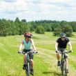 Sport happy couple riding bicycles in coutryside — Stock Photo #6138512