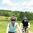 Sport couple riding mountain bicycles in coutryside — Stock Photo #6138519