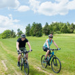 Sport couple riding mountain bicycles in coutryside - Stockfoto