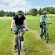 Stock Photo: Sport couple riding mountain bicycles in coutryside