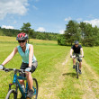 Sport couple riding mountain bicycles in coutryside — Stock Photo #6138534