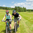Sport mountain biking - man pushing young girl - Stock Photo