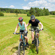 Sport mountain biking - man pushing young girl - Stock fotografie
