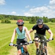 Sport mountain biking - man pushing young girl — Stock Photo
