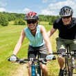 Stock Photo: Sport mountain biking - man pushing young girl