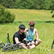 Sport mountain biking couple relax sunny meadows - Stock Photo