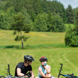 Stock Photo: Sport mountain biking couple relax in meadows