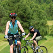 Sport mountain couple biking uphill sunny meadows — Stock Photo