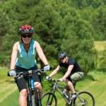 Sport mountain couple biking uphill sunny meadows — Stock Photo