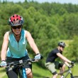 Sport mountain couple biking uphill sunny meadows - Stock Photo