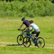 Sport mountain couple biking downhill sunny meadows - Stock Photo