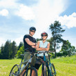 Sport mountain biking couple relax in meadows — Stock Photo