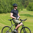 Sportive man mountain biking relax sunny meadows - Stock Photo