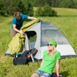Camping couple build-up tent sunny countryside - Stok fotoğraf