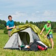 Camping couple build-up tent sunny countryside - Стоковая фотография