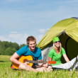 Camping couple playing guitar by tent countryside — Stock Photo #6138630