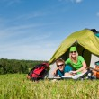 Camping couple lying inside tent summer countryside - Stock Photo