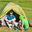 Young camping couple cooking meal outside tent — Lizenzfreies Foto