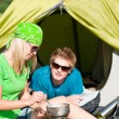 Young camping couple cooking meal outside tent — Stock Photo