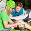 Young camping couple cooking meal outside tent - Lizenzfreies Foto