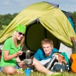 Young camping couple cooking meal outside tent — Stock Photo #6138666