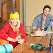 Tramping young couple relax by wooden table - Stock Photo