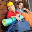 图库照片: Tramping young couple backpack relax by cottage