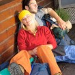 Tramping young couple backpack sleep by cottage - Stock Photo