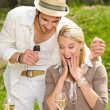 Surprised woman receiving wedding ring sunny terrace — Stock Photo