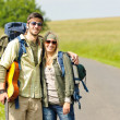 Hiking young couple backpack tramping asphalt road - Stock Photo