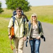Hiking young couple backpack tramping asphalt road - Photo