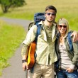 Hiking young couple backpack tramping asphalt road — Stock Photo