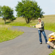 Hitch-hiking young couple backpack asphalt road - Stock Photo