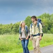 Hiking young couple backpack asphalt road countryside — Stock Photo