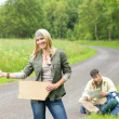Hitch-hiking young couple backpack asphalt road — Foto de Stock