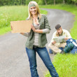Hitch-hiking young couple backpack asphalt road — Stock Photo