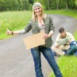 Hitch-hiking young couple backpack asphalt road — Stock Photo #6138876