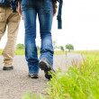 Hiking couple legs backpack on asphalt road - Foto Stock