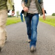 Hiking couple legs backpack on asphalt road — Stock Photo