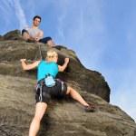 Woman climbing up rock man hold rope — Stock Photo