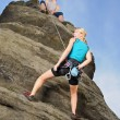 Stock Photo: Womclimbing up rock mhold rope