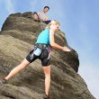 Woman climbing up rock man hold rope — Stock Photo #6138902