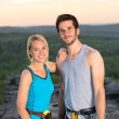 Rock climbing active couple on top sunset — ストック写真