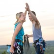 Rock climbing cheerful alpiners on top sunset — Stock Photo
