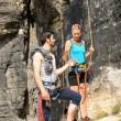 Rock climbing young man showing woman rope — Stok fotoğraf